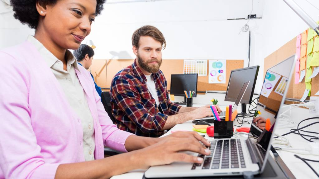woman and man behind a laptop are in an inclusive meeting