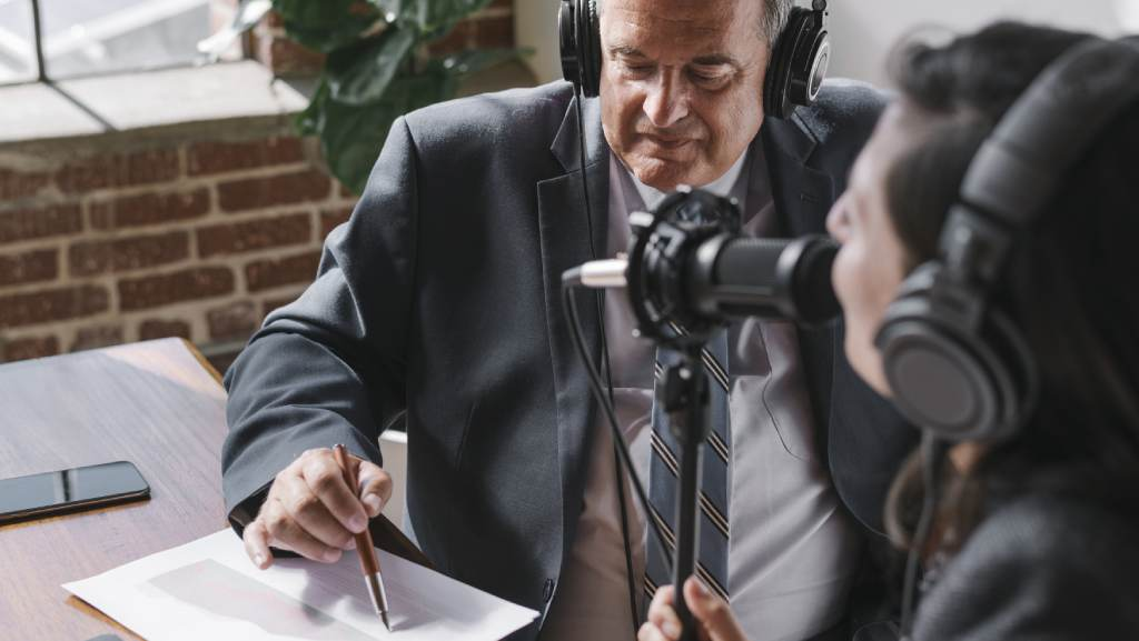 man enjoying the benefits of a podcast transcription from a woman who is podcasting