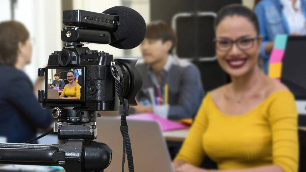 Woman in front of a camera with a microphone